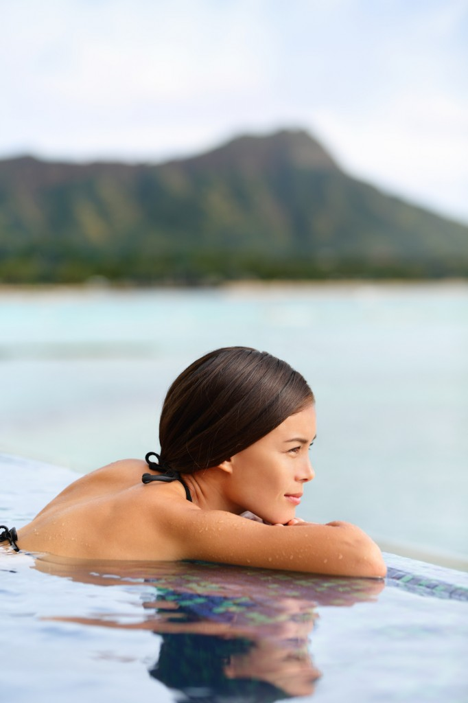 Infinity pool spa hotel resort woman relaxing at sunset overlooking Waikiki beach in Honolulu city, Oahu island, Hawaii, USA. Wellness and relaxation concept for summer vacations.